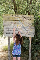 A young girl - about five years old - points on a wooden map. Signage of the River Path. Canyon de Río Lobos Natural Park. Soria. Castilla y León. Spa...