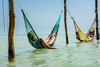Tourist in hammocks on a beach in Isla Holbox, Quintana Roo (Mexico).