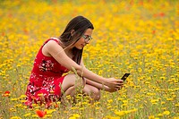 Girl with a red dress taking a photograph to a flower with a mobile in a yellow field.
