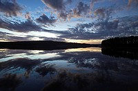 Clouds illuminated by the setting sun are reflected in a quiet lake. Agnsjön, Bredbyn, Västernorrland, Sweden.