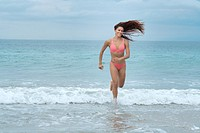 Attractive woman in bikini running at a beach.