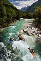 Kayakers shooting the cold emerald green alpine water of the Upper Soca River near Bovec Slovenia with Veliko Spicje mountain in the Julian Alps.