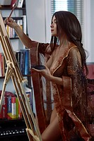 Beautiful young woman sumi-e artist with an easel painting half nude in comfort of her home studio wearing just a sheer robe over her naked body.