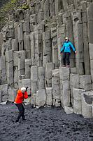 People posing on the basalt columns at Halsanefshellir, a cliff in southern Iceland not far from the village Vík.