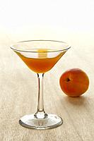 Glass of apricot liqueur and fresh fruit on the background.