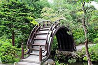 An unusual high arched pedestrian bridge over a stream in a landscaped Japanese Garden in California, USA.