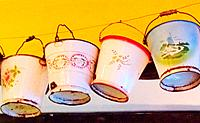 A row of colourful painted buckets.