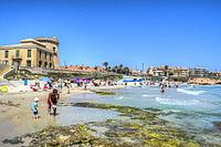 HDR image of the Mediterranean sea laps on to a sandy beach and rocks at Torre de la horadada in Spain.