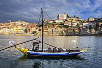 Calem Port wine boat called Rabelo Boat on a Douro River in Vila Nova de Gaia city. Porto city river bank on background.