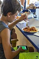 Avon, Outer Banks, North Carolina, USA. Young Boy Eating Lunch while Playing with Mobile Gaming Device.