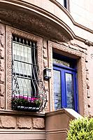 New York City, Manhattan, Upper West Side. Close up of Brownstone Townhouse Entry and Burglar Bar Window with Flower Holder.