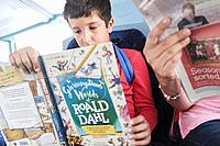 Summer holidays days out-Boy,10,reading a book on the bus,London,England.