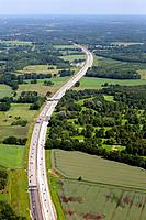Aerial view of agricultural farmland with green fields, forest and a highway passing, Lower Saxonia, Germany, Europe