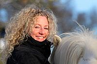 Young blond woman with Icelandic horse, Smiling and looking at the camera, Attenbach, Siegerland, North-Rhein-Westphalia, Germany, Europe.