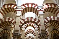 Double red-and-white colored arches inside the Mezquita Mosque and Cathedral in Cordoba, Andalusia, Spain.
