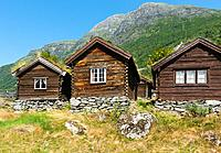 A view across Lovatnet Lake, a traditional Norwegian house sits in the foreground topped with sod roof.
