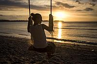 A silhouette of a young woman on a swing in a beach of Gili Air, Gili Islands, Indonesia.