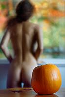 Cute artistic portrait of a blurred back silhouette of a nude woman standing by the window naked looking at fall nature scenery with a pumpkin on the ...