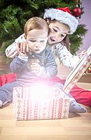 Little brothers opening their presents close to Christmas tree. They are illuminated by magical light from gift box.
