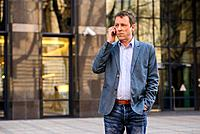 A middle age businessman standing in front of an office building while talking on his phone.