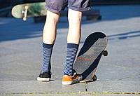 Skateboarding - detail of skateboard and legs with trainers.