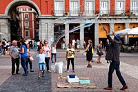 A street artist doing a demonstration inflating a balloon with sparkling water in the Plaza Mayor, Madrid, Spain