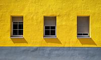Yellow wall with three windows and shutters in different positions , Baden Württemberg, Germany.