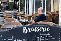 Waiting for his companion a man sits quietly in a brasserie in Pézenas , France, enjoying the weather.