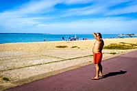 A man looks out to sea dressed in a bathing suit which sits below his stomach.