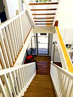 A modern design interior with straight stairs and white paint, Canada.