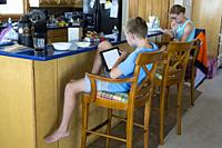 Avon, Outer Banks, North Carolina, USA. KidsPre-teenage and Teenage American Children at Breakfast while Reading their Mobile Gaming Devices.