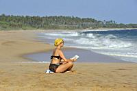 young woman reading sitting on the Tangalle beach, Sri Lanka, Indian subcontinent, South Asia.