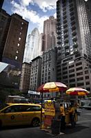 Hot dog vendors prepare fast food to sell in Manhattan where there are a lot of fast food kiosks.