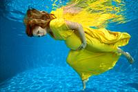 Young pregnant woman in yelow dress under water in the pool.