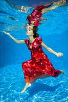 Young pregnant woman in red dress under water in the pool.