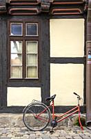 Broken and abandoned bicycle in front of historic half-timbered architecture in Hoelle Alley in the Old Town of Quedlinburg, Saxony-Anhalt, Germany.