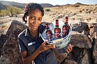 Lodge staff carrying bucket of beer - Huab Under Canvas, Damaraland, Namibia, Africa.