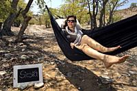 Woman relaxing in Hammock - Huab Under Canvas, Damaraland, Namibia, Africa.