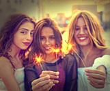 Best friends teen girls with sparklers at sunset in the city filtered image.