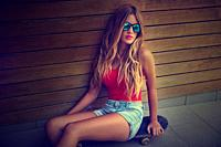 Blond teen girl sit on skateboard in a wood wall with sunglasses filtered image.