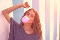 Brunette teen girl bubble gum in a summer beach blue stripes wall filtered image.