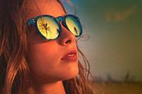 Brunette girl on beach sunglasses with palm tree reflection filtered image.