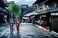 Two girls in bright Yukata kimonos with their obi tied in a bow walking down Yasaka dori street in Kyoto near Kiyomizu-dera after an autumn rain. Higa...