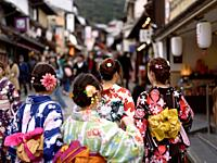 Group of teenage girls in bright Yukatas, summer kimonos, walking towards Kiyomizu-dera on Matsubara dori street in Kyoto. Higashiyama, Kyoto, Japan.
