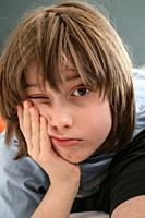Young boy with messy brown hair leaning his cheek on his hand with one eye open in Brussels, Belgium.