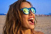 Brunette girl on beach sunglasses with palm tree reflection.