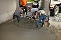 Work crew pouring cement from a cement truck shute over wire mesh on a residential garage floor and spreading with shovel and rake Toronto Ontario Can...