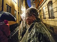 Sweden, Stockholm. Ghost walk in Old Town or Gamla Stan, man with rain poncho.