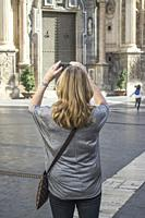 Female tourist taking a photograph with a iPhone in the Cathedral Square of Murcia City Spain.