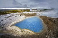 Geothermal Hot Spring Area with Strokkur Geyser in the background erupting, Iceland.